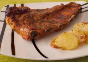 Costillas al horno en plato con patatas al horno