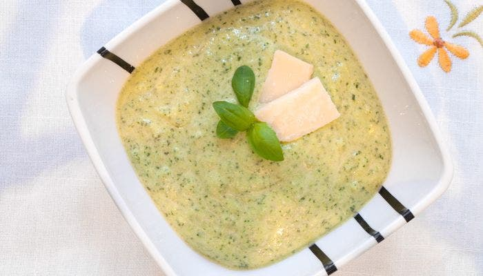 Presentación de la salsa pesto adornada con albahaca y parmesano