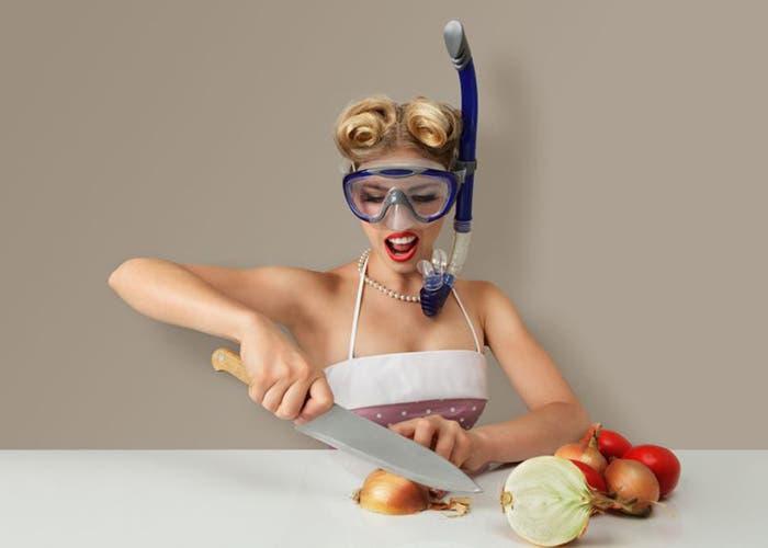 Mujer cortando cebolla llevando gafas de buceo