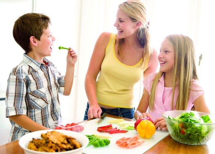 Un niño y una niña en la cocina con su madre