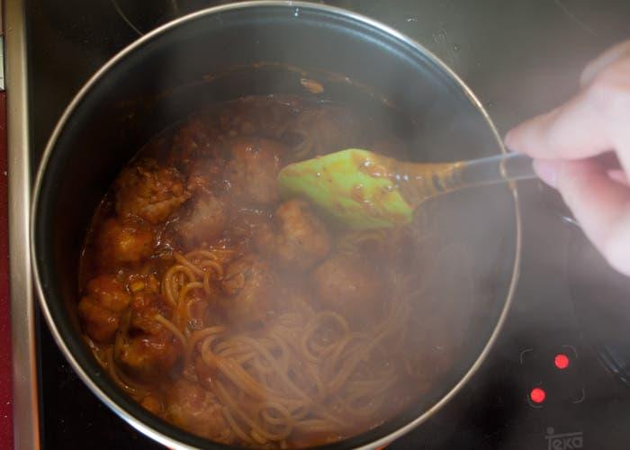 Incorporar a la salsa con albóndigas los espaguetis al dente