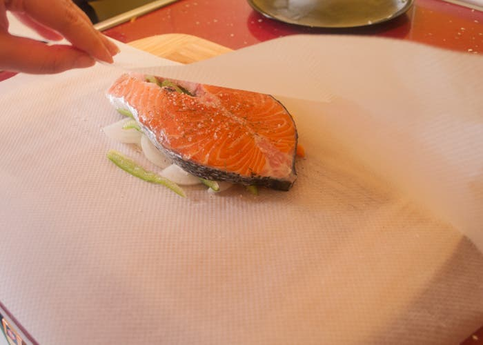 Cerrar paquete con salmón y verduras dentro