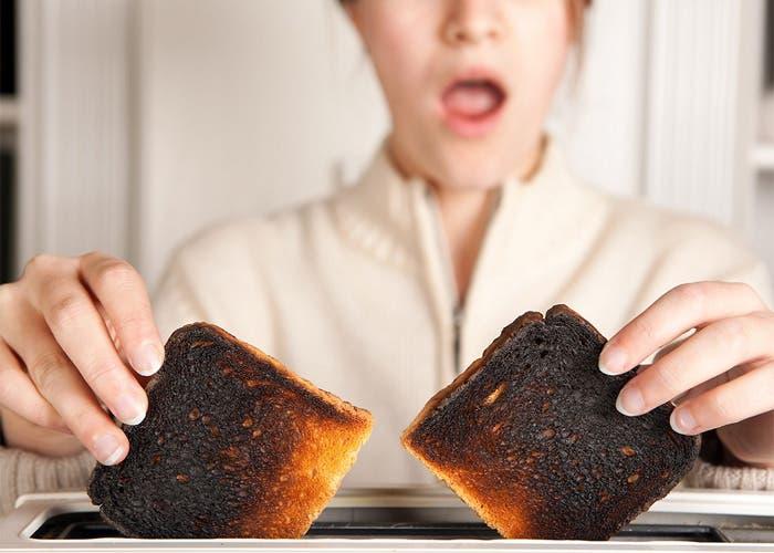 Mujer sostienen sorprendida un par de tostadas quemadas