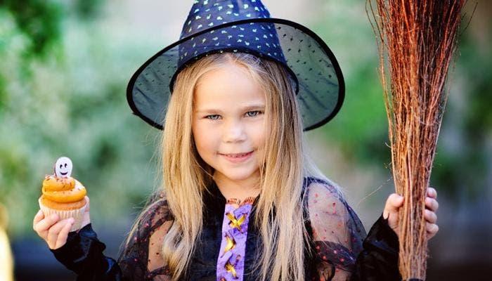 Niña disfrazada de bruja con cupcake de halloween