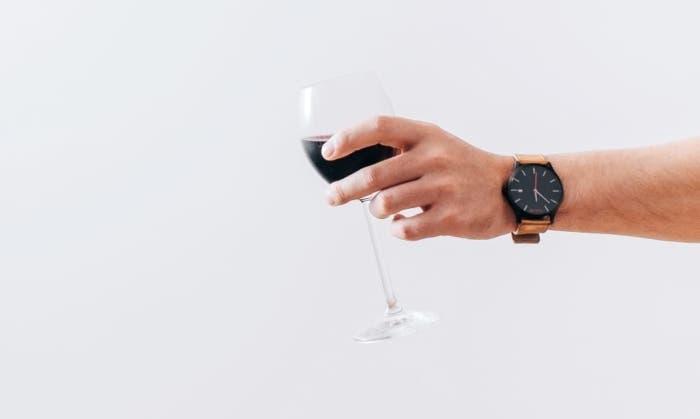 ofreciendo copa de vino tinto
