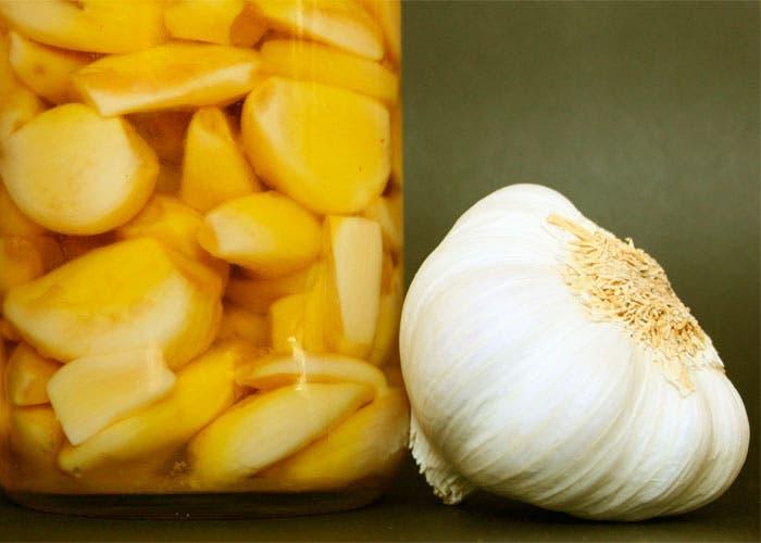 Ajos blanco en aceite y cabeza de ajo entera
